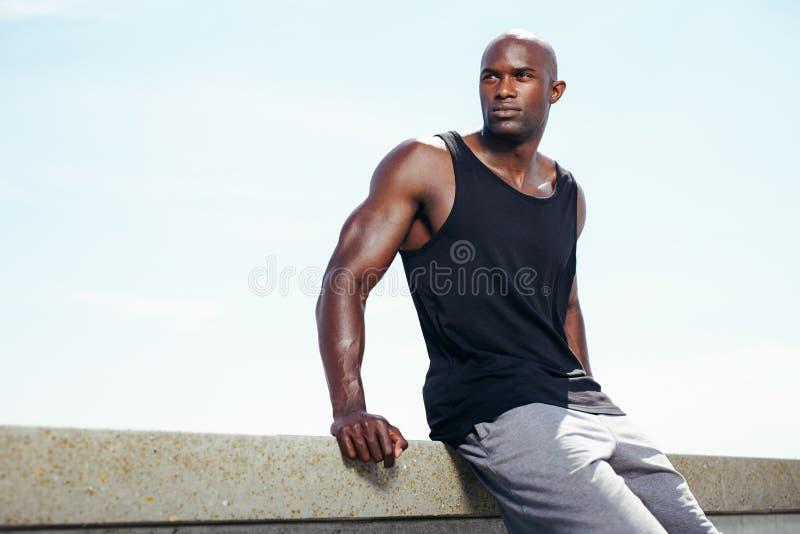 Mięśniowy młody człowiek siedzi outdoors patrzeć daleko od przy copyspace obrazy stock
