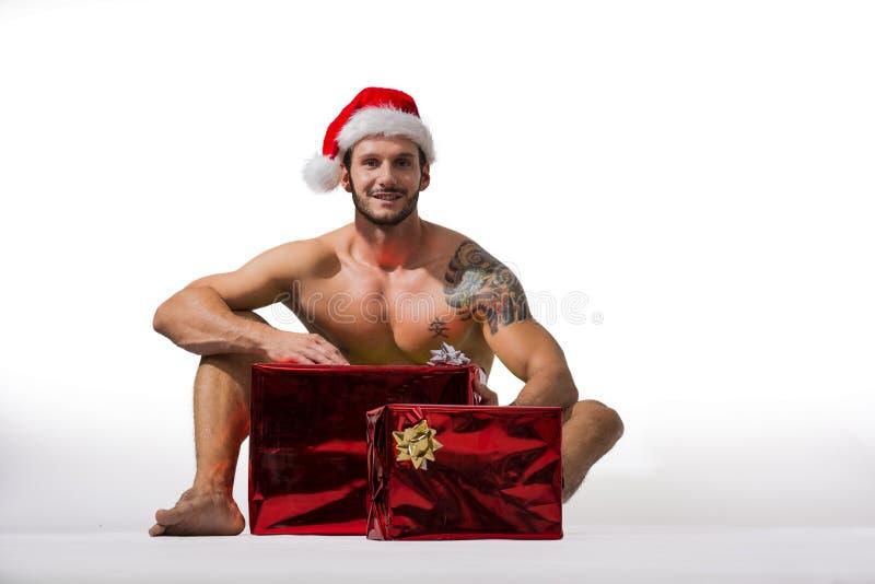 Mięśniowy młody człowiek w Święty Mikołaj kapeluszu z Bożenarodzeniowym prezentem zdjęcie royalty free