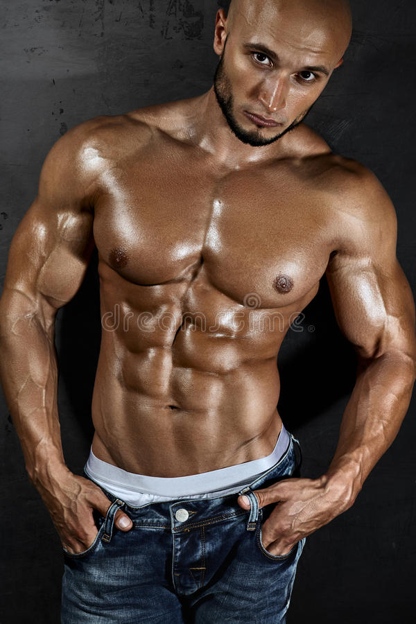 Mięśniowy młody seksowny facet pozuje w studiu obrazy stock
