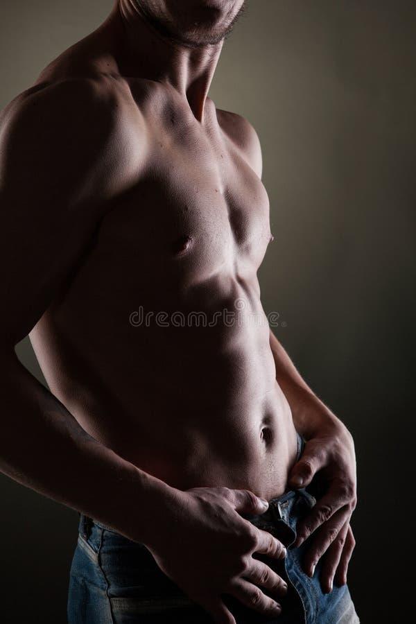 Mięśniowy nagi mężczyzna na czerni zdjęcia stock