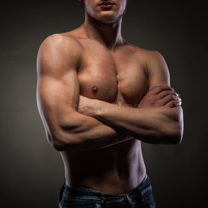 Mięśniowy nagi mężczyzna na czerni fotografia stock