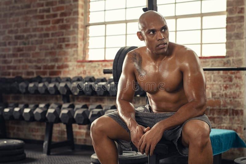 Mięśniowy przepocony mężczyzna odpoczywa w gym zdjęcia royalty free
