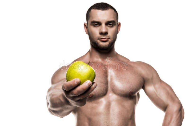 Mięśniowy sportowa mienia jabłko odizolowywający na białym, zdrowym łasowania pojęciu, obrazy stock
