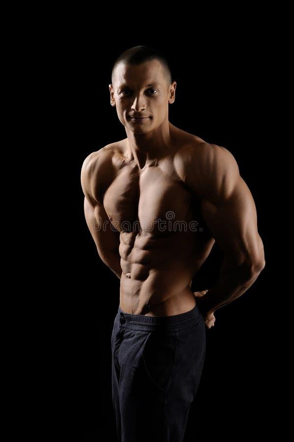 Mięśniowy sprawność fizyczna mężczyzna na czarnym tle zdjęcie stock