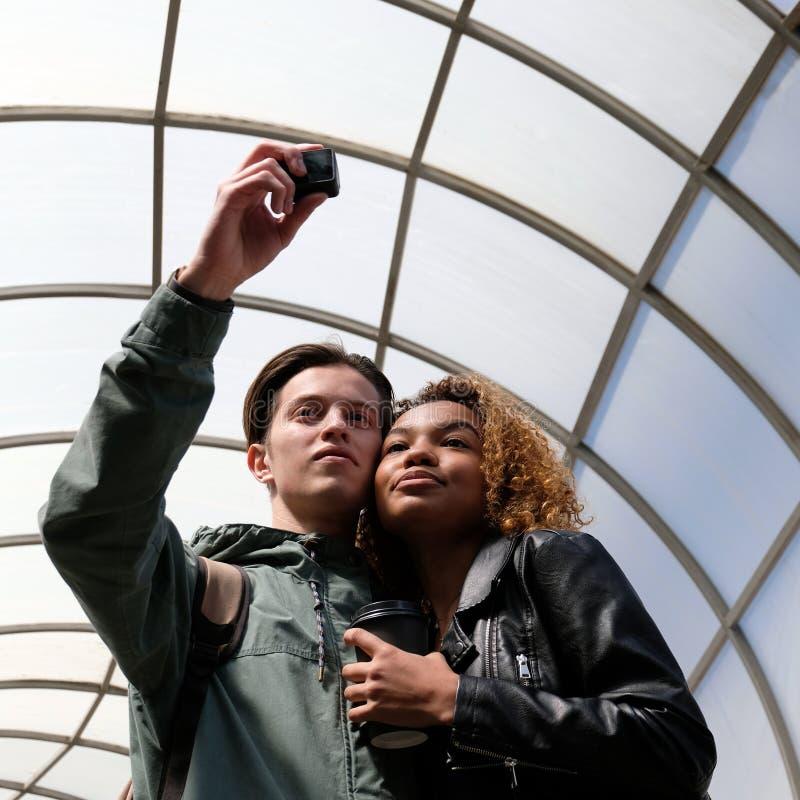 Międzynarodowa przyjaźń piękna młoda czarna dziewczyna i biały facet Enamored ucznie biorą obrazki one obraz stock