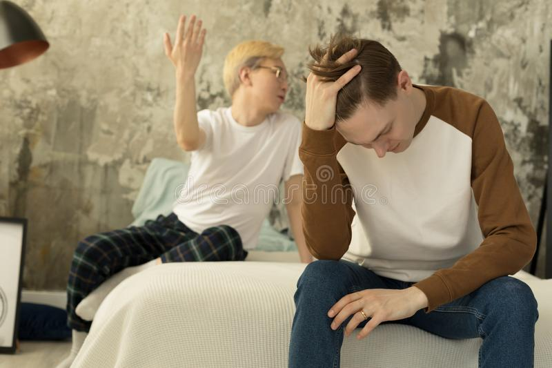 Międzynarodowi homoseksualistów partnery ma rozmowę w loft nowożytnej sypialni podczas gdy wydający czas zdjęcia stock
