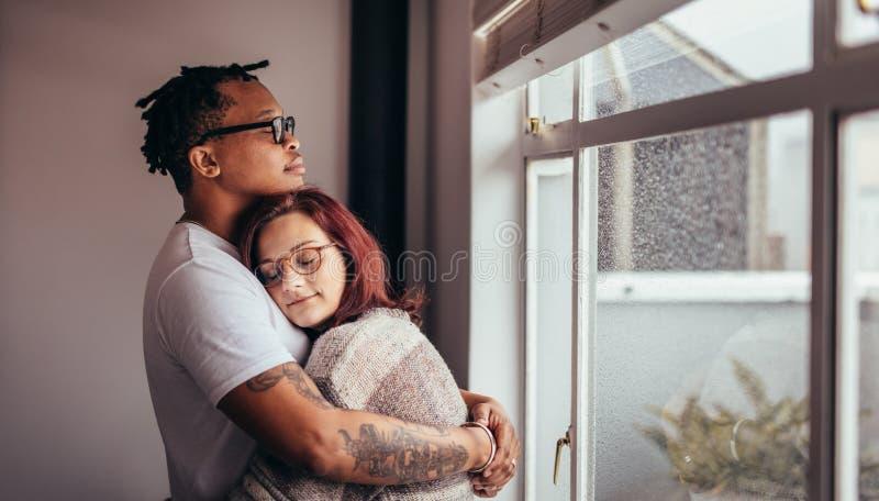 Międzyrasowa para ściska blisko okno fotografia stock