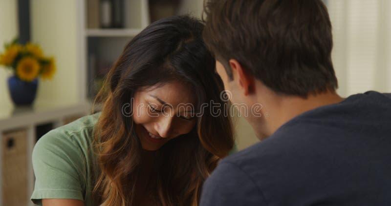 Międzyrasowa para opowiada w domu i słucha zdjęcie stock