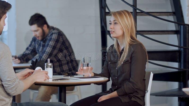 Międzyrasowa para opowiada w sklep z kawą obraz stock