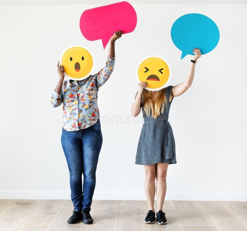 Międzyrasowe kobiety trzyma ekspresyjnego emoticon stawiają czoło wyrazów twarzy ogólnospołecznych środki, gawędzą pojęcie i zask zdjęcie stock