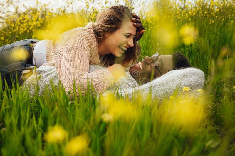 Międzyrasowy pary lying on the beach na trawie i śmiać się obraz royalty free