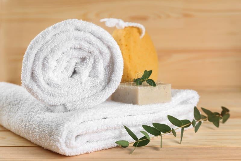 Miękcy ręczniki, prysznic gąbka i mydło na drewnianym stole, obrazy stock