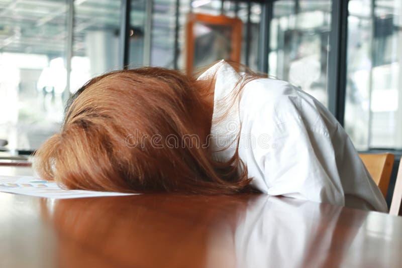Miękka ostrość zmęczona zaakcentowana młoda biznesowej kobiety chyłu puszka głowa na biurku w biurze fotografia stock