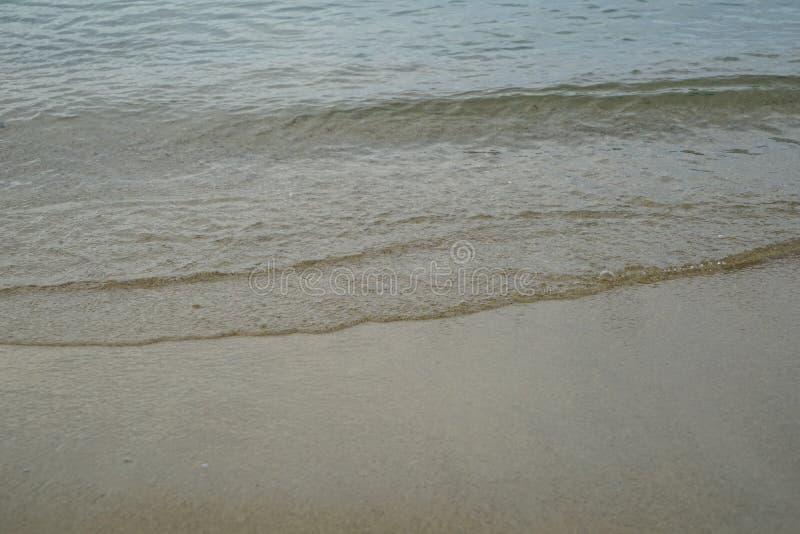 Miękka pastelowa czysta piaskowata plaża z świeżą jasną wody morskiej i światła bąbla fala wykłada tło i copyspace na Ornos brzeg zdjęcia royalty free