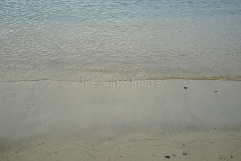 Miękka pastelowa piaskowata plaża z świeżym kryształem - jasny wody morskiej fala linii tło i copyspace na Ornos brzeg zdjęcia royalty free