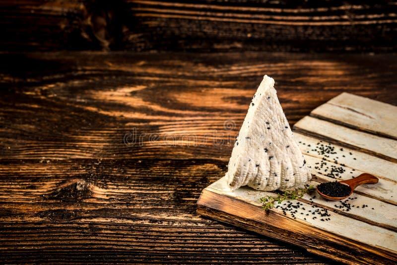 Miękki Adyghe ser z czarnym kminem na nieociosanym tle Przestrze? dla teksta fotografia royalty free