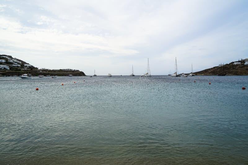 Miękki sceniczny piękny seascape z żeglowanie łodziami, jachtami, jasnym niebem, górą i białym budynku tłem, Ornos plaża fotografia royalty free
