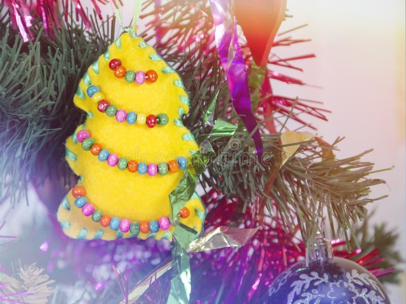 Miękkiej części zabawka w postaci żółtej choinki z koralikami na nowego roku drzewie zdjęcie royalty free
