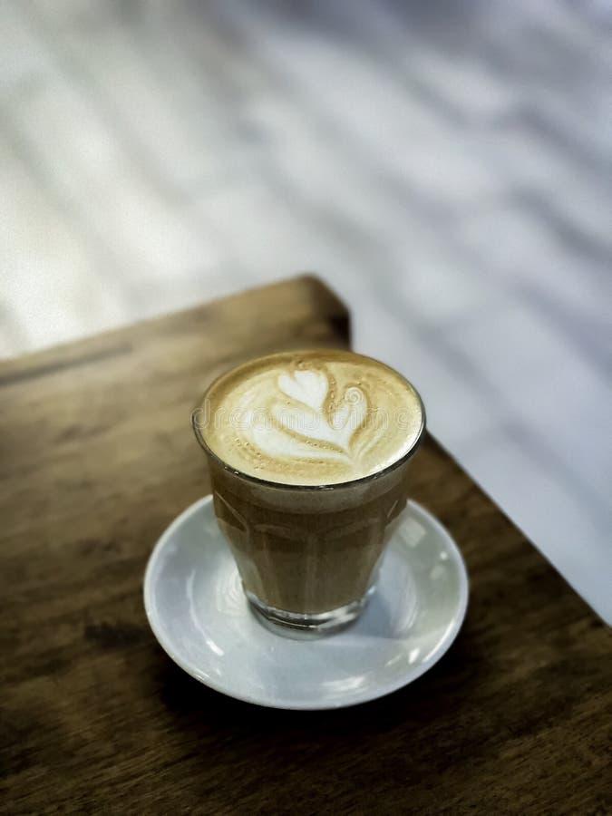 Miękkiej ostrości gorący kawowy latte i zamazany tło zdjęcia stock