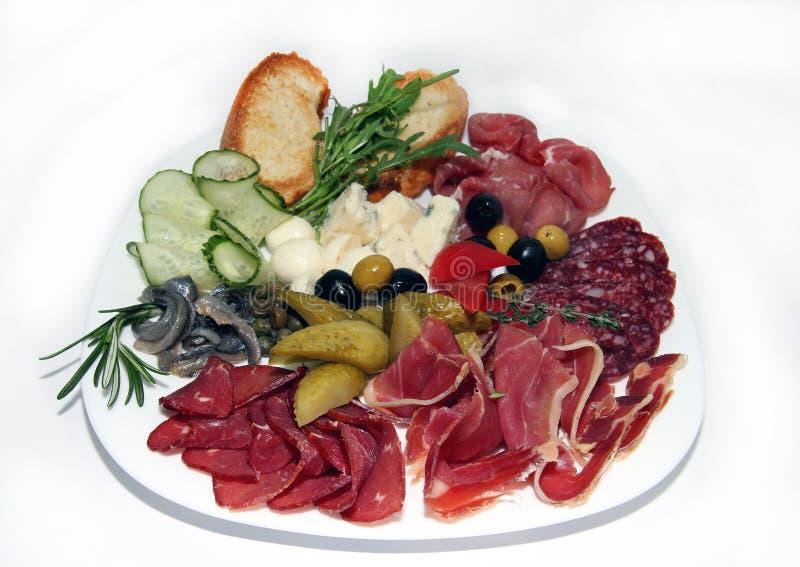 Mięsa, kiełbasa, grzanka, warzywa i ser, są na talerzu zdjęcia royalty free