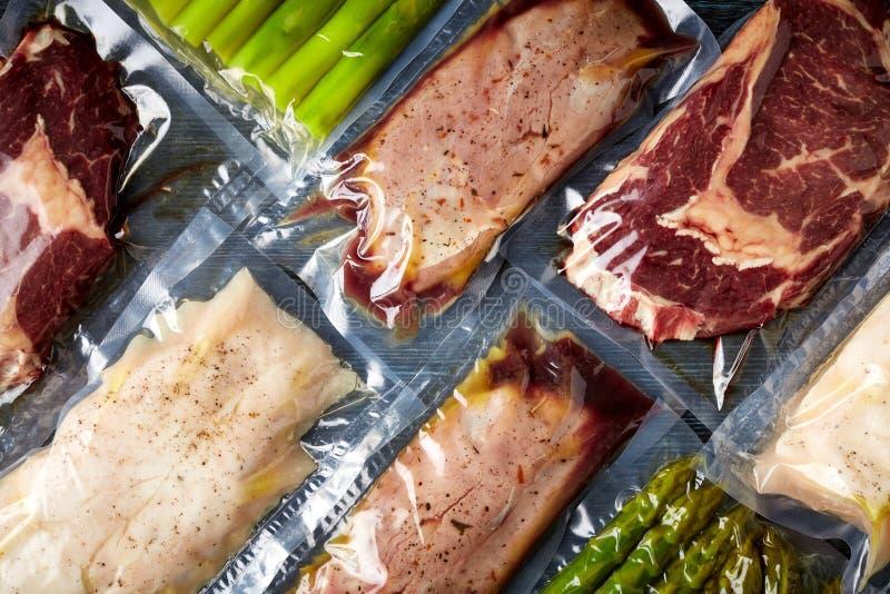 Mięsna i szparagowa próżnia pieczętująca na czerń stole od above, obraz stock