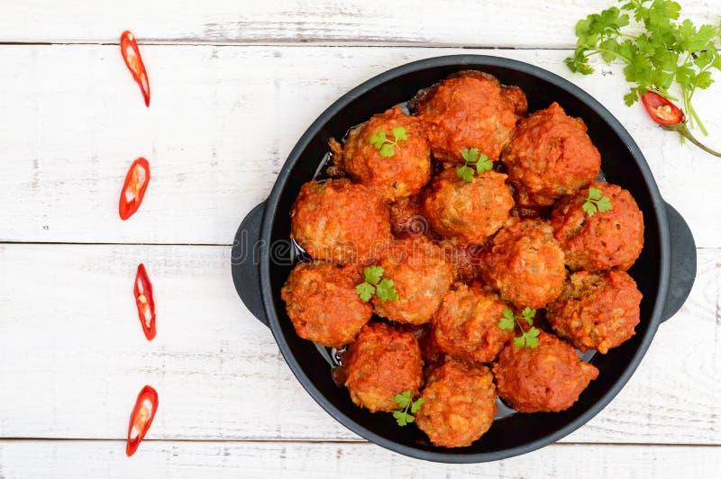 Mięsne piłki w korzennym pomidorowym kumberlandzie słuzyć na ciskającej żelaznej niecce na białym drewnianym tle zdjęcie stock