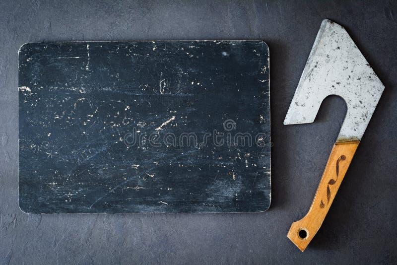 Mięsny cleaver i stara czarna tnąca deska zdjęcie royalty free