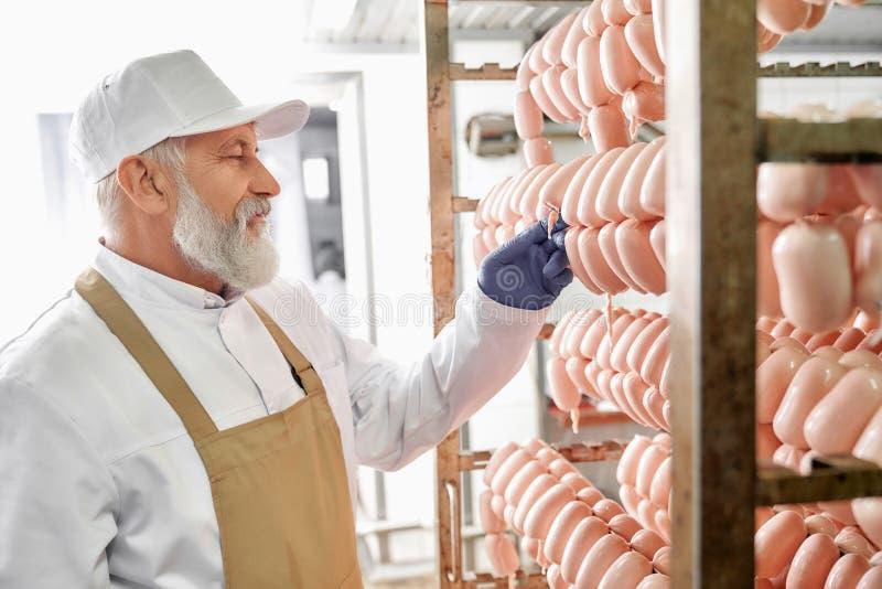 Mięsny fabryczny produkcja pracownik obserwuje kiełbasy obraz royalty free