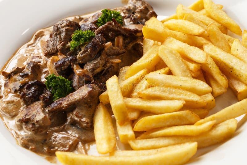Mięsny goulash i smażyć grule w talerzu na odosobnionym białym tła zbliżeniu zdjęcie stock