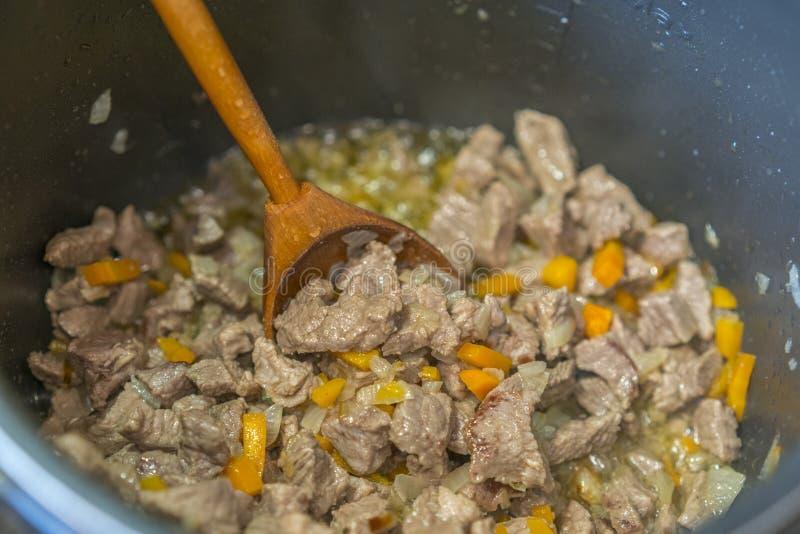 Mięsny gulasz z warzywami i ziele Gulasz w drewnianej łyżce Przygotowanie gulasz, wołowina w rondlu obraz royalty free