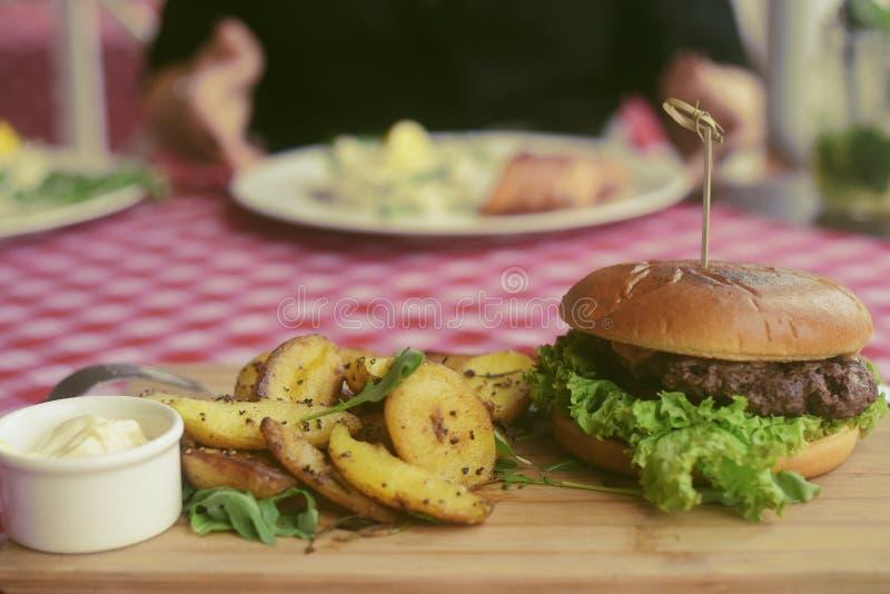 Mięsny hamburger z dłoniakami, majonezowe grule na drewnianej desce cookery cutlet naczynia karmowy p??miska restauraci styl Jedz fotografia stock