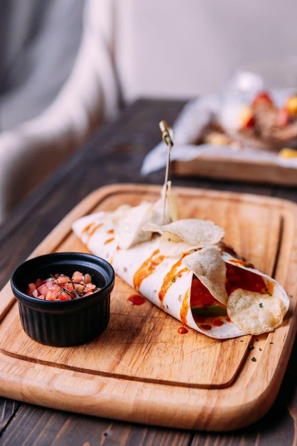 Mięsny kebab z układami scalonymi nakrywa z kumberlandem i słuzyć z pomidorową sałatką na drewnianym talerzu zdjęcia royalty free