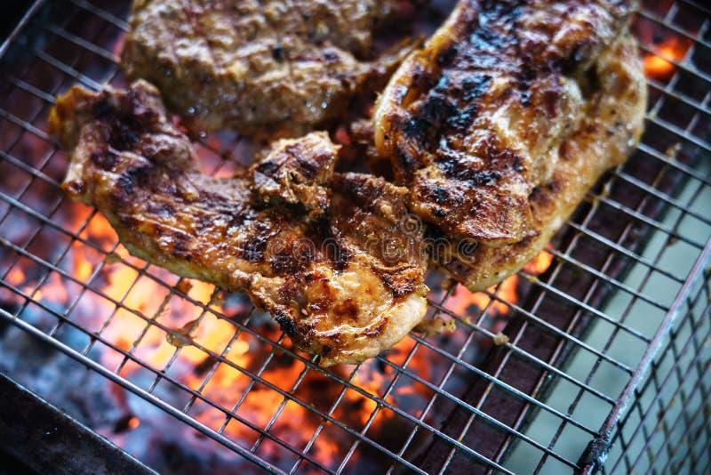 Mięso na grillu z płomieniem na terenach odkrytych grilla zdjęcie stock