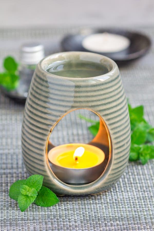 Miętówka istotny olej w aromat lampie na szarość matuje z zdroju tłem obraz stock