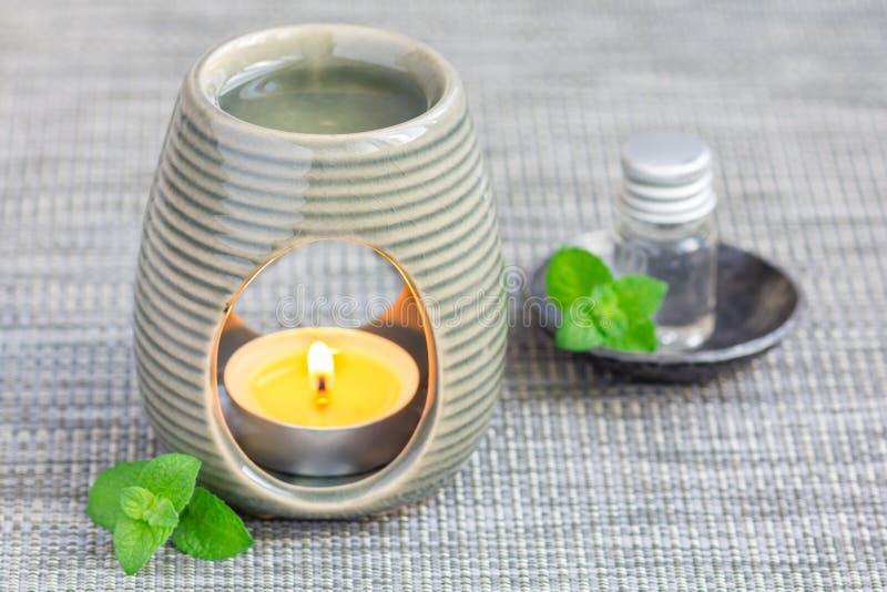 Miętówka istotny olej w aromat lampie na szarość matuje z zdroju tłem obraz royalty free