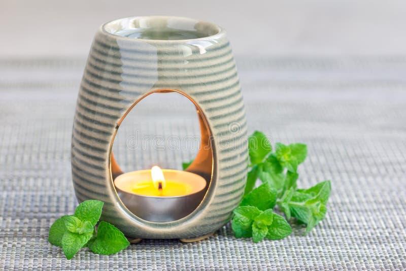 Miętówka istotny olej w aromat lampie na szarość matuje z zdroju tłem, kopii przestrzeń obraz royalty free