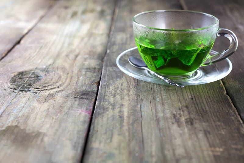 Miętowa herbata w szklanej filiżance na stole obrazy stock