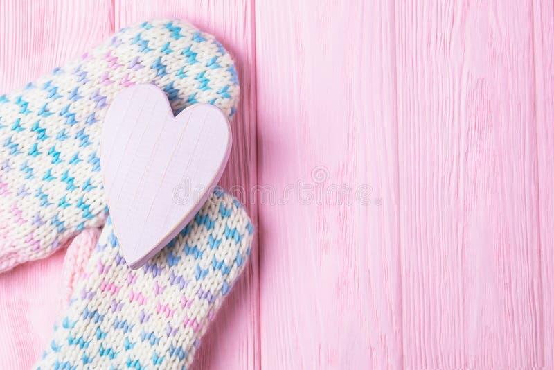 miłość ciepła Walentynki ` s dnia tło Trykotowe woolen rękawiczki trzyma drewnianego różowego serce kosmos kopii obrazy stock
