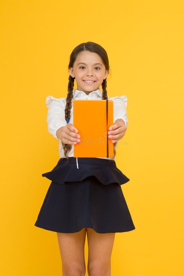 Miłość czyta dla przyjemności Śliczny mały uczeń trzyma czytelniczą książkę na żółtym tle Urocza mała dziewczynka uczy się obraz stock