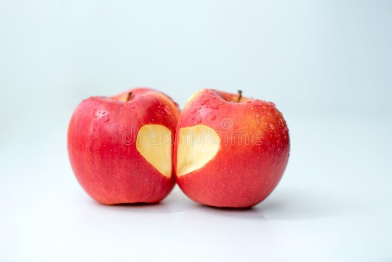 Miłość dwa jabłek pojęcie z starannie naciętym sercem w skórze dojrzały czerwony jabłko na bielu stole zdjęcie royalty free