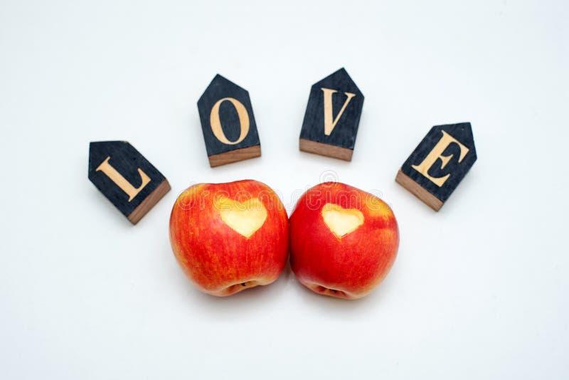 Miłość dwa jabłek pojęcie z starannie naciętym sercem w skórze dojrzały czerwony jabłko na bielu stole obrazy stock