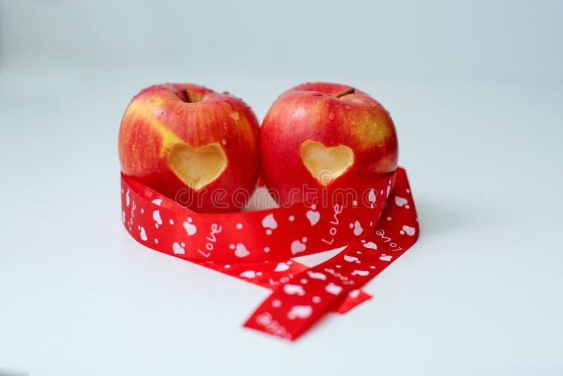 Miłość dwa jabłek pojęcie z starannie naciętym sercem w skórze dojrzały czerwony jabłko na bielu stole obraz stock