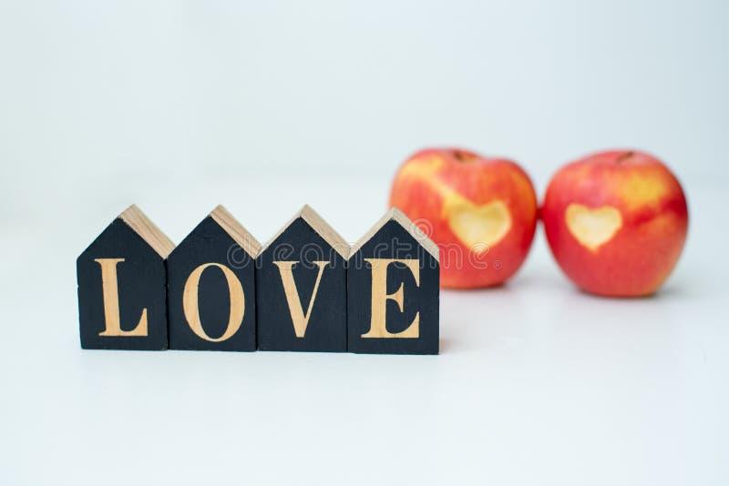 Miłość dwa jabłek pojęcie z starannie naciętym sercem w skórze dojrzały czerwony jabłko na bielu stole obrazy royalty free