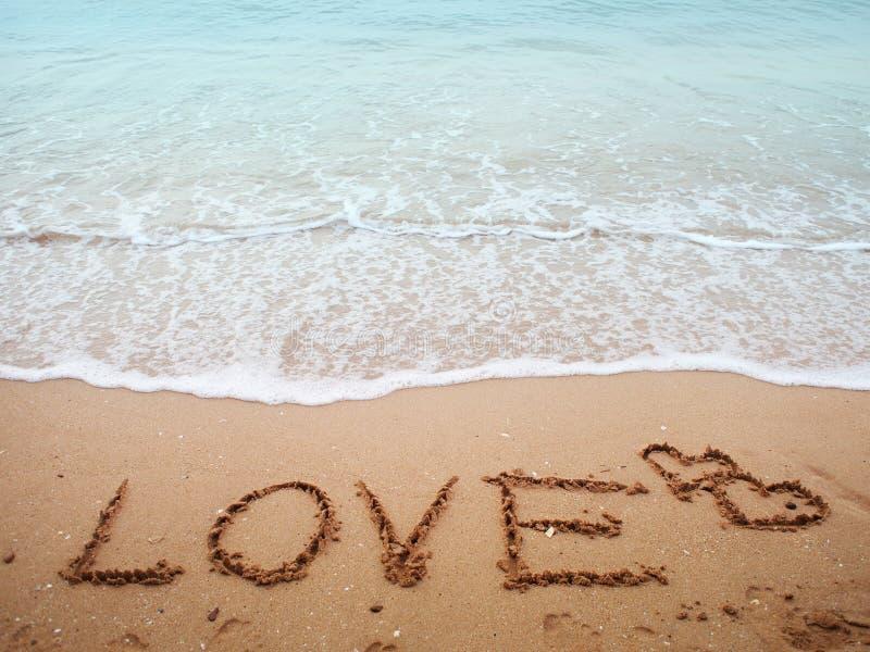 Miłość tekst na piasek plaży obraz stock