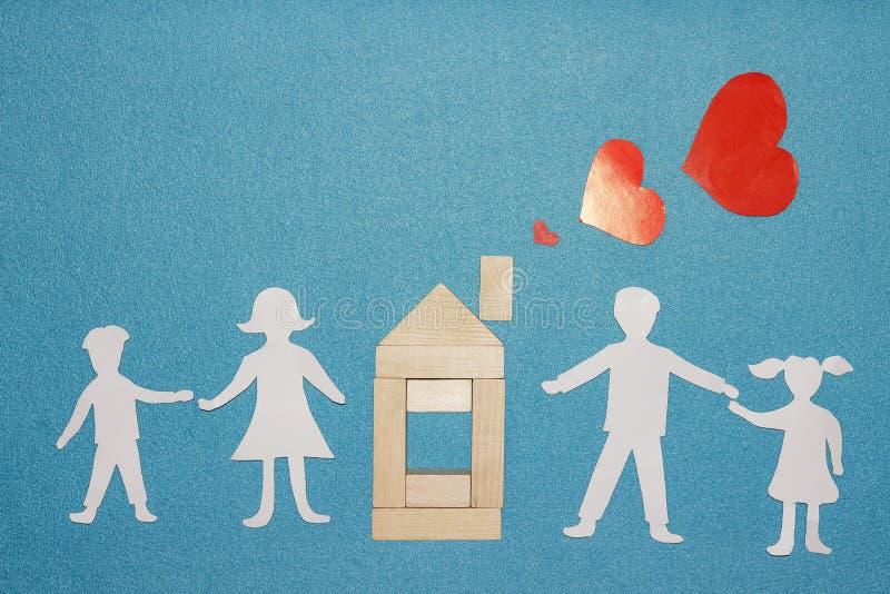 Miłość w domu i rodzinnym pojęciu Papierowe rodzinne mienie ręki i drewniany dom z czerwonymi sercami od komin drymby na błękitny zdjęcia royalty free