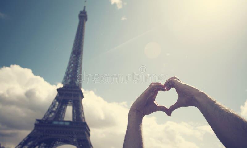 Miłość w Paryż - ręki tworzy kierowego kształt przed Eiff obraz royalty free
