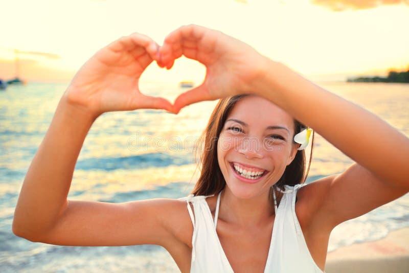 Miłość wakacje - kobieta pokazuje serce na plaży zdjęcie royalty free
