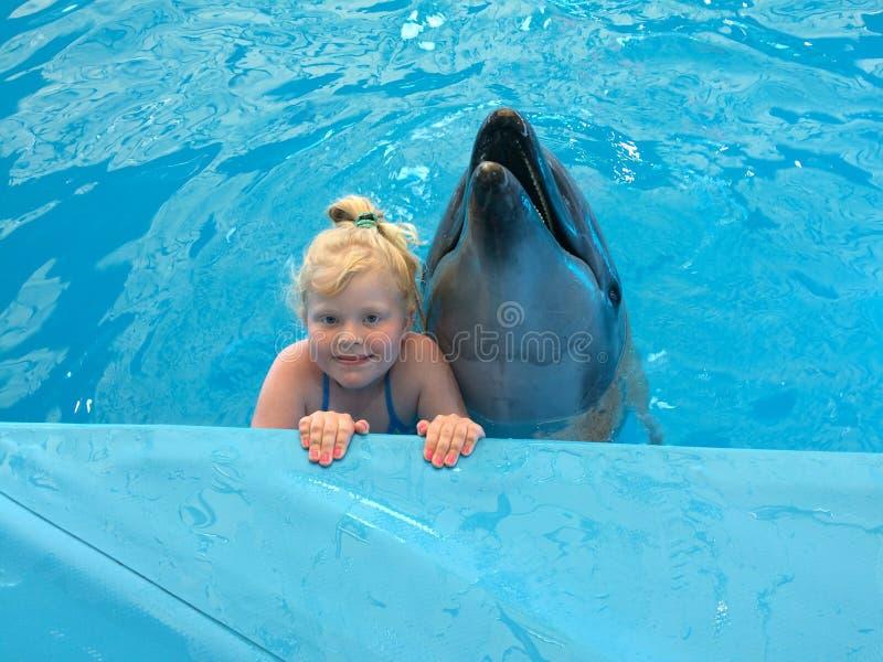Miłość zwierzęta - mała dziewczynka pozuje z delfinem w basenie dolphinarium obrazy royalty free