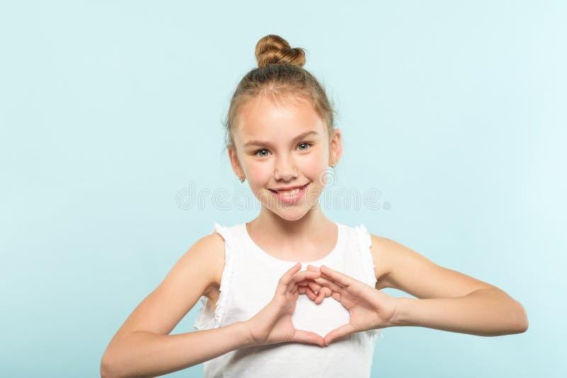 Miłości emoci uśmiechnięta dziewczyna robi kierowym kształt rękom zdjęcia stock