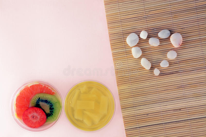 Miłości i bielu kamienny kierowy pojęcie z galaretowymi panny cotta owoc na różowym bambusowym tle fotografia stock
